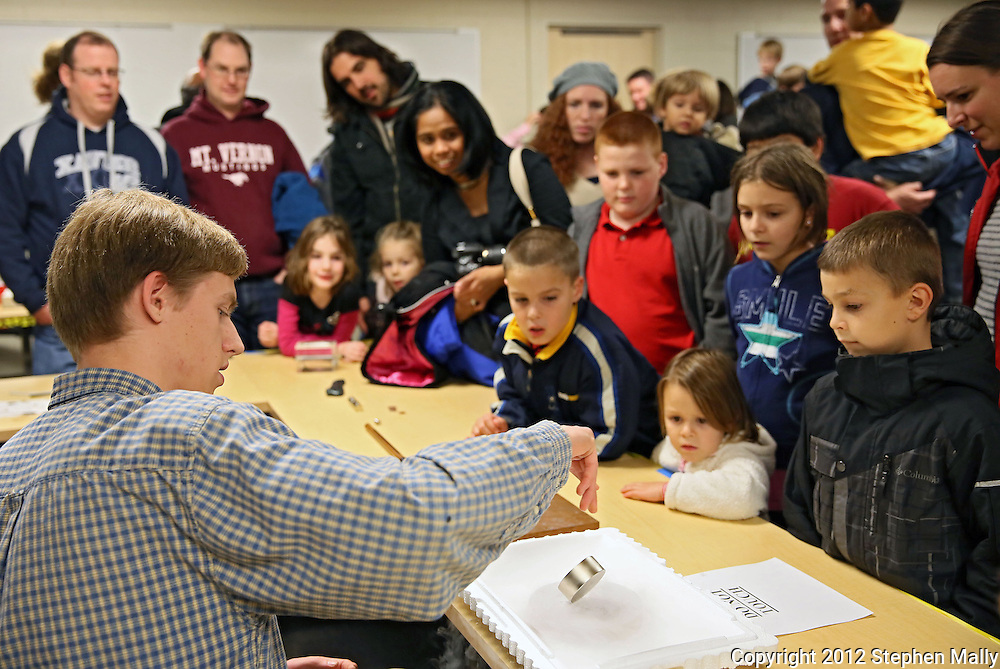 John Talmage, 16, of Walker, gives a demonstration on magnets to kids and parents during the 10th annual Playground of Science at Peterson Hall on the Coe College campus in Cedar Rapids on Thursday, October 25, 2012. Talmage, who is homeschooled, is taking a physics course at Coe College.