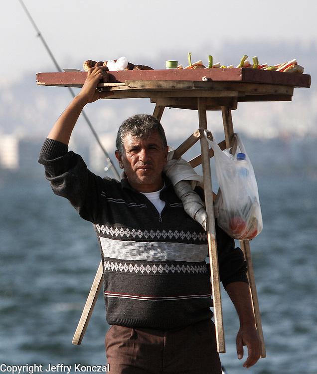A man carries a stand of food through Kordon Boyu Dinlenme Alanı park in Izmir, Turkey