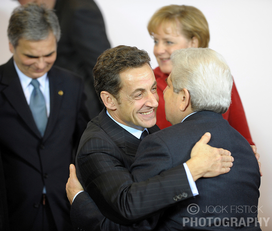 Nicolas Sarkozy, France's president, front left, greets Dimitris Christofias, president of Cyprus, front right, while Angela Merkel, Germany's chancellor, back right, and Werner Faymann, Austria's chancellor, back left, find their places during the family photo session at the European Summit in Brussels, Belgium, Thursday, Dec. 11, 2008. (Photo © Jock Fistick)