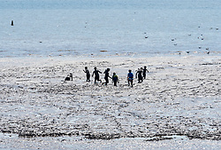 © Licensed to London News Pictures;30/05/2020; Weston-super-Mare UK. People play in the mud as the tide goes out on a hot sunny weather on the beach and promenade at the seaside in Weston-super-Mare, on the last weekend before some more restrictions under the coronavirus lockdown are to be eased by the Government. From Monday groups of up to 6 people from different households will be able to meet outside but must maintain social distancing to prevent the spread of the Covid-19 virus. There has been an outbreak of Covid-19 at Weston General Hospital which has now been traced to an accommodation block inside the hospital grounds. The outbreak had been blamed on visitors to Weston coming from outside the area. Photo credit: Simon Chapman/LNP.