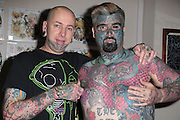 "EXCLUSIVE<br /> Britain's most tattooed man ""King Of Ink Land"" has had is nipple removed in this latest bizarre twist King of ink as he is now known<br /> spent friday morning having his nipple removed,<br /> <br /> King of ink said ""I have never really found my nipples attractive. In fact I just didn't like them. My girlfriend will miss them as she use to enjoy biting them something that comes a little bit erotica, However I am pleased to finally have them removed. It was not in the least painful however the next week or two I will be a,little sore.<br /> <br /> he went to say<br /> <br /> We will always respect our bodies.<br /> <br /> We believe it is our right to explore our world, both physical and supernatural, through spiritual body modification.<br /> <br /> We promise to always grow as individuals through body modification and what it can teach us about who we are and what we can do.<br /> <br /> We vow to share our experiences openly and honestly in order to promote growth in mind, body, and soul.<br /> <br /> We honor all forms of body modification and those who choose to practice in safe and consensual ways.<br /> <br /> We also promise to respect those who do not choose body modification.<br /> <br /> We support all that join us in our mission and help those seeking us in need of spiritual guidance.<br /> <br /> We strive to share a positive message with everyone we encounter, in order to act as positive role models for future generations in the body modification community.<br /> <br /> We always uphold basic codes of ethics and encourage others to do the same.<br /> when asked about his latest body transformation he replied <br /> <br /> ""I may practice rituals and body modification without prejudice or discrimination. By acting responsibly and with integrity, I wish to observe our sincerely held religious beliefs without restriction""<br /> <br /> Photo shows: King if Ink pictured with his girlfriend ""Queen of Ink Land"" and ""Dr Evil Mac"" or his real name Mac McCarthy<br /> ©Exclusivepix"