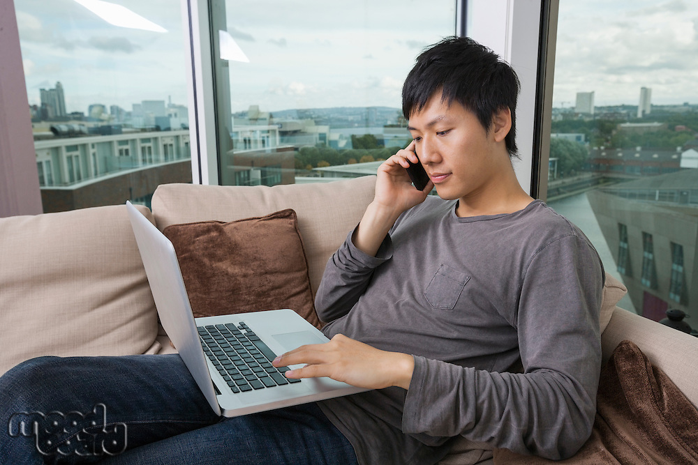 Asian mid adult man on call while using laptop in living room
