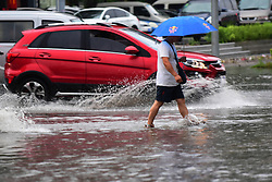 August 3, 2017: Changchun, Jilin, China - A pedestrian and a car wade through a water-logged road in Changchun. Heavy rain has battered Jilin Province since Wednesday evening. Water resources department and metrological service of Jilin issued a yellow alert for flood. China has a four-tier color-coded weather warning system, with red the most severe, followed by orange, yellow and blue. (Credit Image: © Lin Hong/Xinhua via ZUMA Wire)