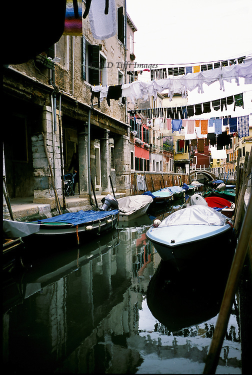 Workaday Venice: canal view in Castello, with peoples' boats moored alongside, laundry hanging overhead on lines strung across the canal, reflections in the canal water...
