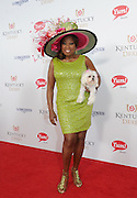 Star Jones, with her dog Pinky, walks the Kentucky Derby Red Carpet, Saturday, May 3, 2014, in Louisville, Ky. Longines, the Swiss watchmaker known for its famous timepieces, is the Official Watch and Timekeeper of the 140th annual Kentucky Derby. (Photo by Diane Bondareff/Invision for Longines/AP Images)