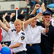 NLD/Amsterdam/20100807 - Boten tijdens de Canal Parade 2010 door de Amsterdamse grachten. De jaarlijkse boottocht sluit traditiegetrouw de Gay Pride af. Thema van de botenparade was dit jaar Celebrate, politie boot