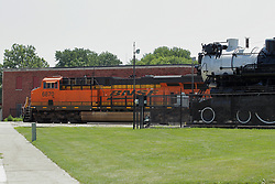 A Burlington Northern Santa Fe Diesel Freighter travels through Galesburg at the Amtrak Train Depot and Railroad Museum passing an old Steam Locomotive that is on display.
