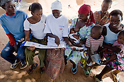 Community volunteer explaining the importance of using a treated mosquito net to villagers. Northern Ghana, Thursday November 13, 2008.