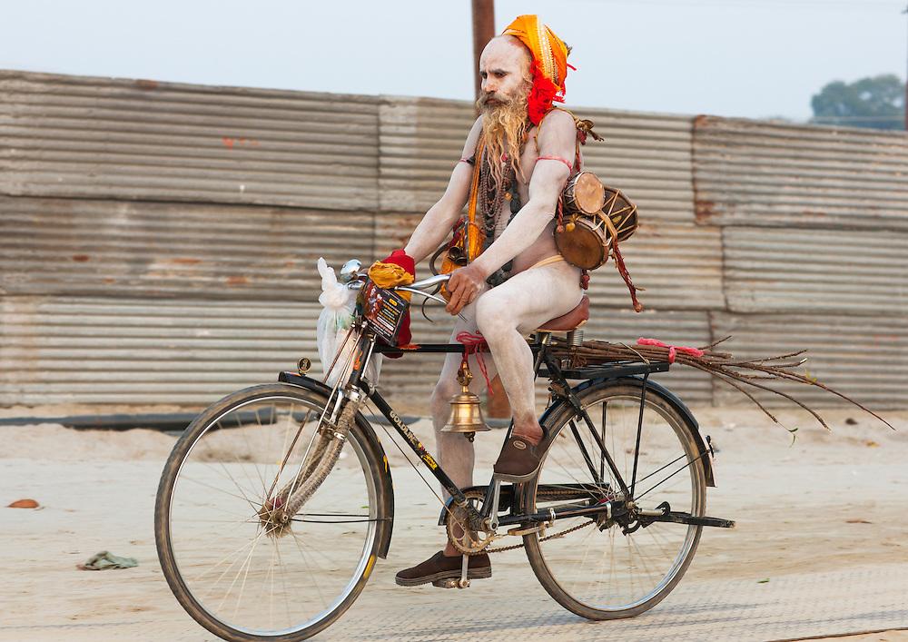Naga Sadhu on a bike, Maha Kumbh Mela festival, world's largest congregation of religious pilgrims. Allahabad, India.