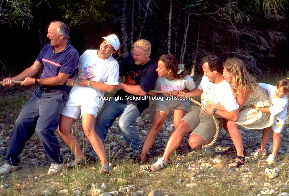 Family playing tug of war on island picnic. Les Cheneaux Islands Lake Huron Cedarville Michigan USA
