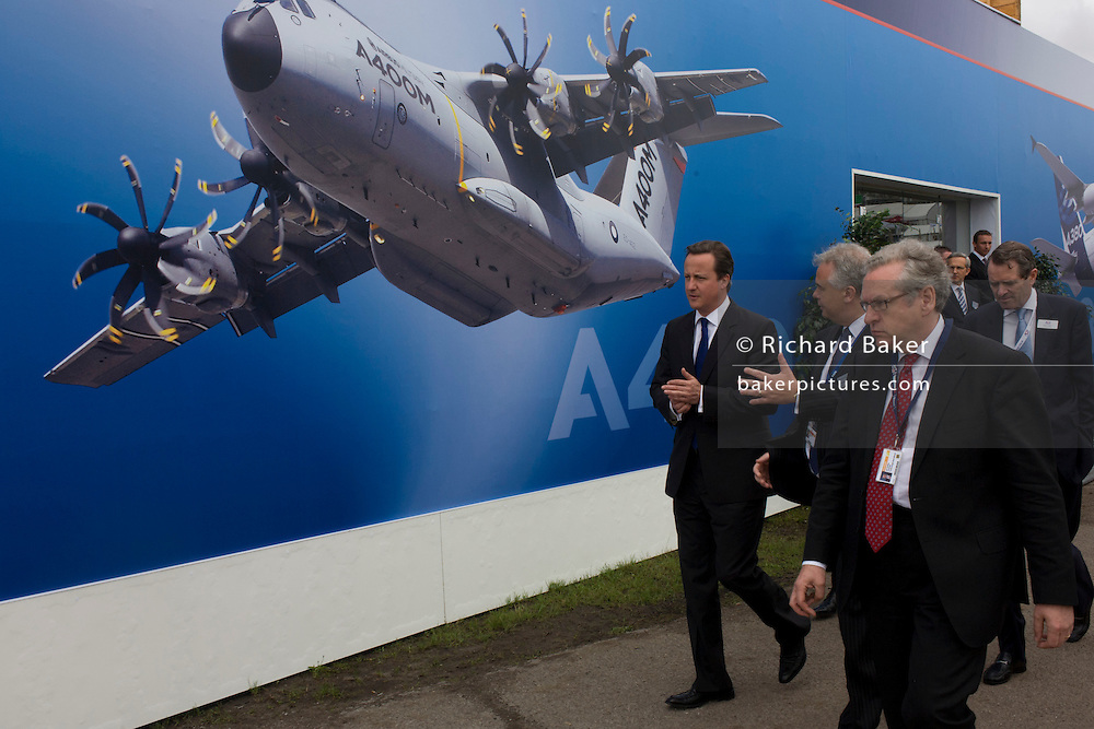 Farnborough, UK 09/07/12 British Prime Minister David Cameron walks past one of the Airbus exhibition stands at the Farnborough Air Show, England. Helping to launch this expo held for the international aviation and aerospace industries, Cameron toured stands to help promote trade and investment for this 48th airshow (FIA)and hailed the phenomenal success of the UK aerospace industry and its critical importance to growth and jobs.Farnborough is attended by an international business audience including 83 trade and military delegations from over 43 countries..