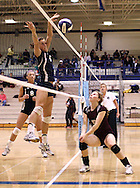 Xavier junior Alex Saxen (6) tips the ball over the net to a waiting Mt Vernon junior Sarah Ryan in their match at the Westside Volleyball Invitational at Jefferson High School in Cedar Rapids on Saturday October 10, 2009. Mt Vernon won the match 21-7, 21-17.