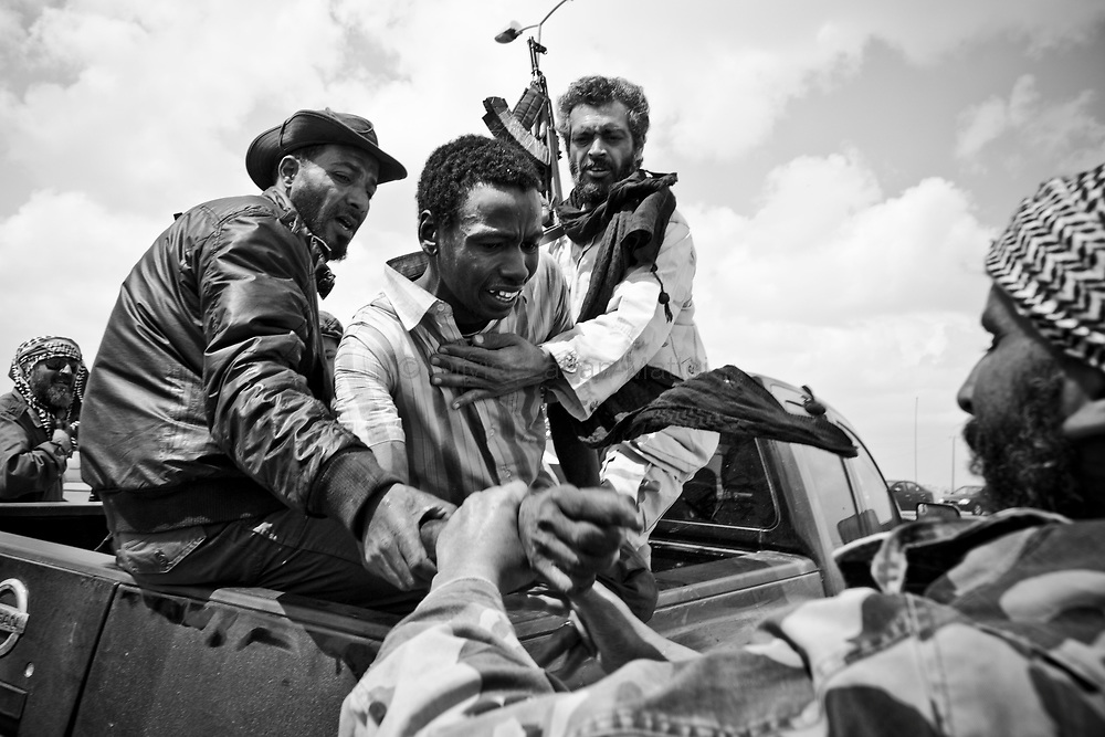 Un homme d'origine tchadienne suspecté d'être un mercenaire à la solde du colonel Kadhafi est arrêté et emmené en vue d'être interrogé, le 1er avril 2011 à la sortie de la ville d'Aj Dabiya.