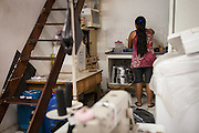 A Bolivian lady in the kitchen of an immigrant sewing workshop in, São Paulo, Brazil. <br /> <br /> Frequently immigrants work, eat and sleep in the same room. <br /> <br /> Nearly 90% of the immigrants arriving in São Paulo end up working in the textile industry. <br /> <br /> Today there are about 20,000 sewing shops in São Paulo and 400,000 immigrants working in the clothing sector.