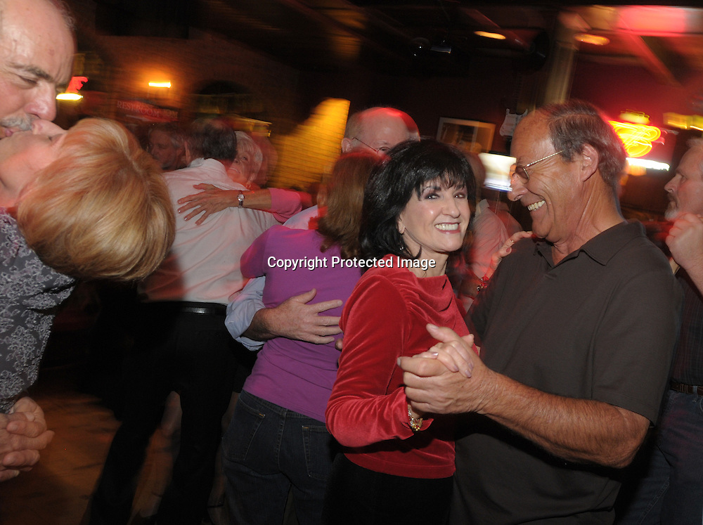 Kathleen Belani (in the red shirt) dances with a will male partner while enjoying the late night dance scene at the Bourban St. bar in the main downtown square of The Villages, Fla., Saturday, Jan. 17, 2009. (Photo by Phelan M. Ebenhack)
