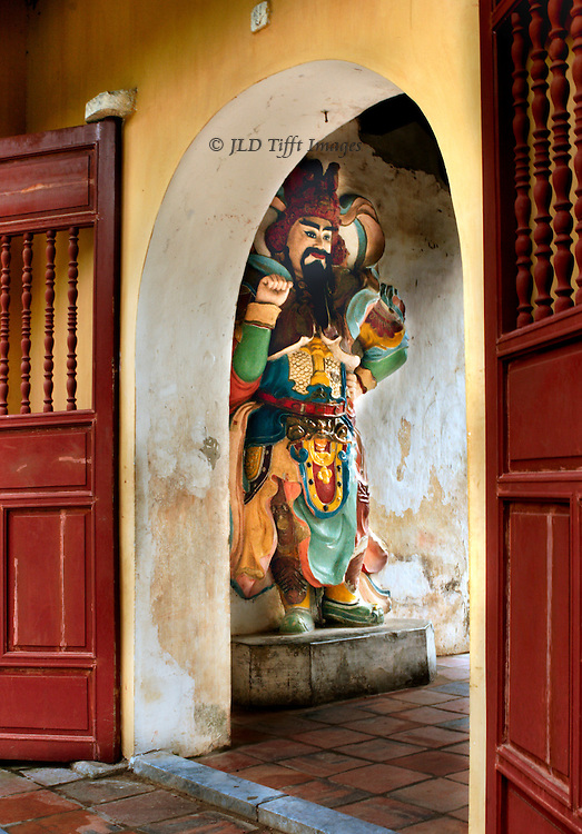 Thien Mu (Huong ) Pagoda, on the Perfume River near Hue, Vietnam: fierce and colorful guardian statue figure in ancient military garb seen through an arched doorway.