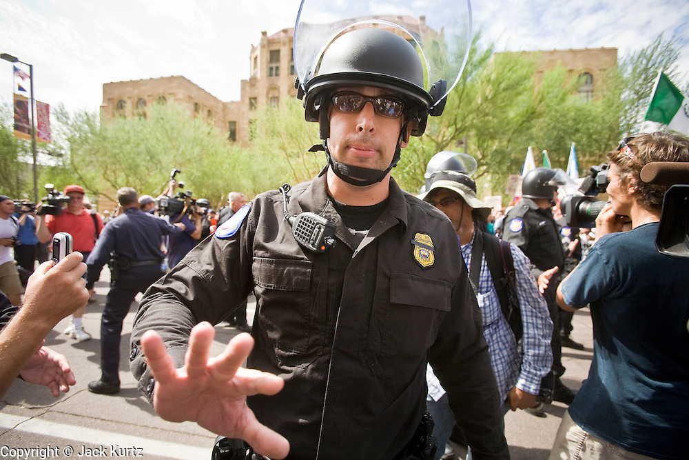 """29 JULY 2010 - PHOENIX, AZ: Phoenix police clear off the street before arresting folks who engaged in civil disobedience. Dozens of people were arrested during protests against SB 1070 across central Phoenix Thursday. US Judge Susan Bolton's ruling Wednesday stopped four of SB 1070's more than a dozen provisions from going into effect. She wrote, """"The court also finds that the United States is likely to suffer irreparable harm if the court does not preliminarily enjoin enforcement of these sections,"""" she states in the ruling. """"The balance of equities tips in the United States' favor considering the public interest.""""   PHOTO BY JACK KURTZ"""