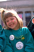 Girl age 6 smiling big at St Patricks day parade.  St Paul  Minnesota USA