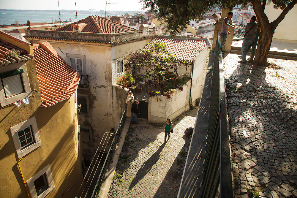 A lady passing by a staired-alley in Alfama district in Lisbon.