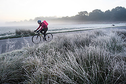 © Licensed to London News Pictures. 28/10/2019. London, UK. A man cycles through a frost and mist covered landscape on a bright winter morning in Richmond Park, London. The UK is due to see brighter weather over the next few days, following days of heavy rain which caused flooding in parts. Photo credit: Ben Cawthra/LNP