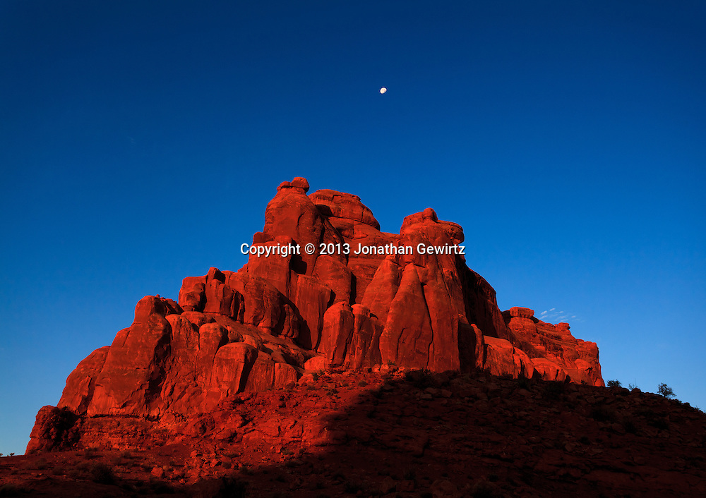 The rising sun illuminates red rocks in Arches National Park, Utah. WATERMARKS WILL NOT APPEAR ON PRINTS OR LICENSED IMAGES.<br /> <br /> Licensing: https://tandemstock.com/assets/92801227