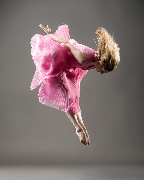 Contemporary female dancer, Sarah Brower, jumping in a pink dress, taken in the photo studio on a gray background. Photograph taken in New York City by photographer Rachel Neville.