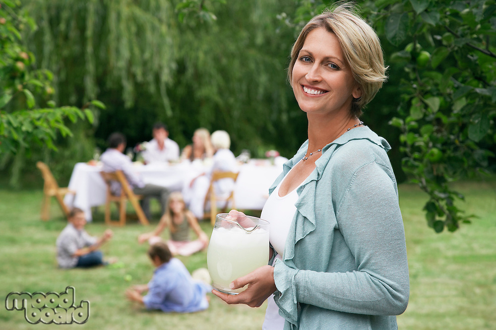 Woman with pitcher of lemonade in garden family members in background
