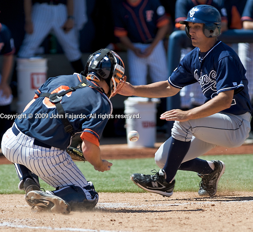 U.C. Irvine base runner D.J. Crumlich goes for home plate before Fullerton catcher Billy Marcoe can get a handle on the ball in the Big West Conference game against U.C. Irvine at Goodwin Field, Fullerton CA, Sunday April 5, 2009.  The Titans win in ten innings 5-4.