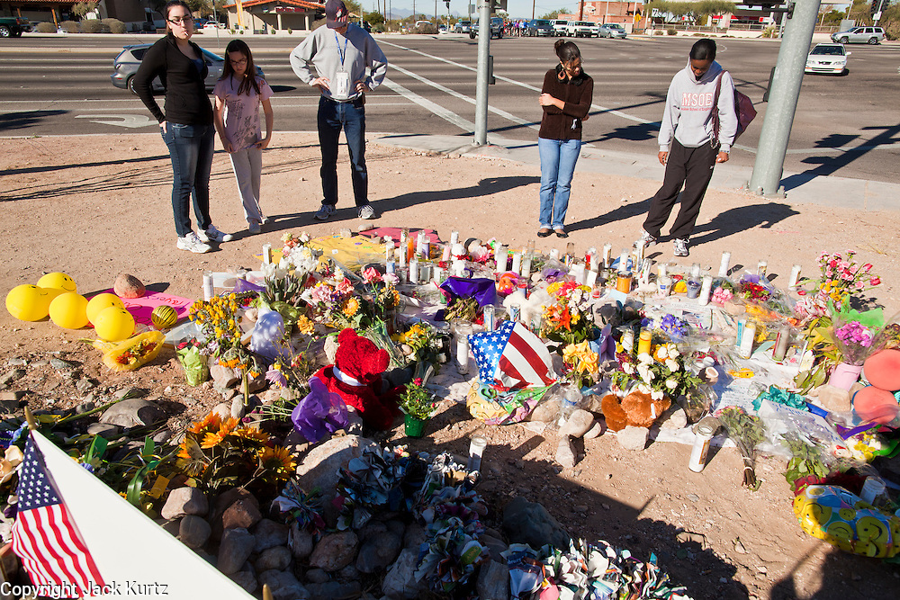 """15 JANUARY 2010 - TUCSON, AZ:    People visit the memorial for Congresswoman GABRIELLE GIFFORDS and others shot Sat. Jan. 8 at the intersection of Ina and Oracle Roads in Tucson, AZ, Saturday, January 15. Six people were killed and 14 injured in the shooting spree at a """"Congress on Your Corner"""" event hosted by Arizona Congresswoman Gabrielle Giffords at a Safeway grocery store in north Tucson on January 8. Congresswoman Giffords, the intended target of the attack, was shot in the head and seriously injured in the attack but is recovering. Doctors announced that they removed her breathing tube Saturday, one week after the attack. The alleged gunman, Jared Lee Loughner, was wrestled to the ground by bystanders when he stopped shooting to reload the Glock 19 semi-automatic pistol. Loughner is currently in federal custody at a medium security prison near Phoenix.  PHOTO BY JACK KURTZ"""