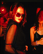 Pouting woman wearing sunglasses in a club