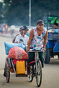 06 JUNE 2014 - IRRAWADDY DELTA,  AYEYARWADY REGION, MYANMAR: A man on a pedicab brings onions to the market in Pantanaw, a town in the Irrawaddy Delta (or Ayeyarwady Delta) in Myanmar. The region is Myanmar's largest rice producer, so its infrastructure of road transportation has been greatly developed during the 1990s and 2000s. Two thirds of the total arable land is under rice cultivation with a yield of about 2,000-2,500 kg per hectare. FIshing and aquaculture are also important economically. Because of the number of rivers and canals that crisscross the Delta, steamship service is widely available.   PHOTO BY JACK KURTZ