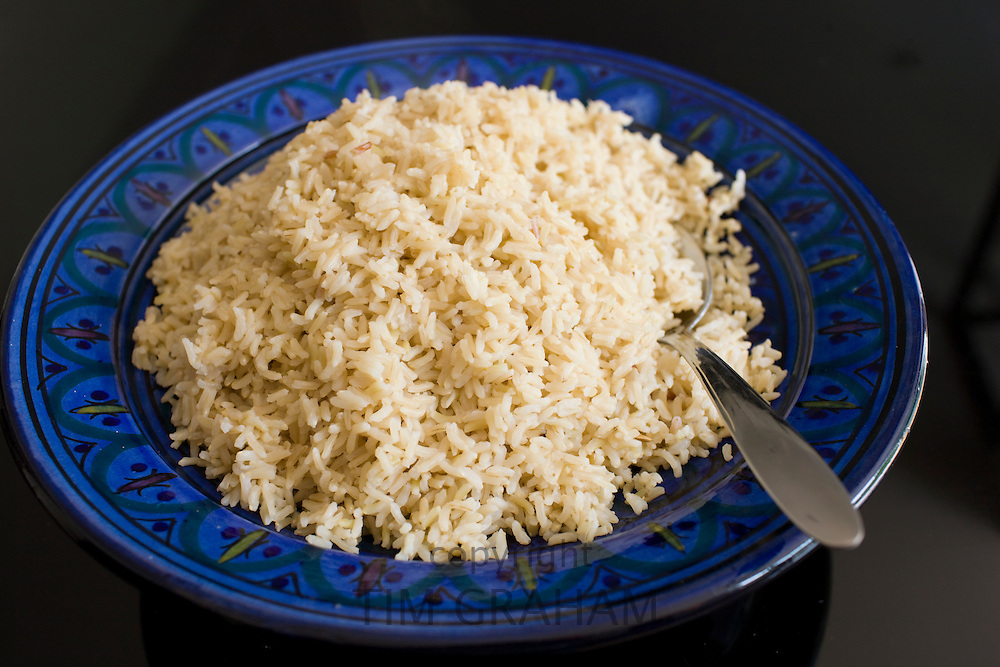Bowl of brown wholegrain rice and spoon. Rice has become an expensive commodity as its in short supply.