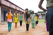 Tabasum Khatun, 14, (centre) and her best friend Anju Kumari, 13, (left) are practising a Karate salute to their instructor during a class in Algunda village, pop. 1000, Giridih District, rural Jharkhand, India.