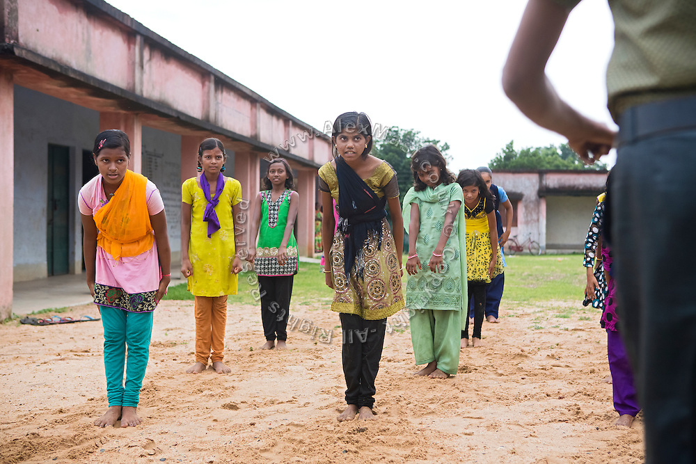 Tabasum Khatun, 14, (centre) and her best friend Anju Kumari, 13, (left) are practising a Karate salute to their instructor during a class in Algunda village, pop. 1000, Giridih District, rural Jharkhand, India.