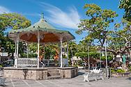 Gazebo bandstand (kiosko) in Plaza Principal, Old Town Puerto Vallarta, White wrought iron park benches in Zona Romantica, the town square city center.