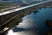 Nederland, Limburg, Gemeente Maasgouw,, 07-03-2010; binnenvaartschip op het Julianakanaal ten oosten van Stevensweert. Het kanaal is aangelegd in het kader van de Maaskanalisatie. In de voorgrond een zandwinplas / oude Maasarm..Barge on the Juliana Canal east of Stevensweert. The canal was built as part of the Meuse Canalization. In the foreground a pond, result of Sand extraction  / old Maasarm..luchtfoto (toeslag), aerial photo (additional fee required).foto/photo Siebe Swart