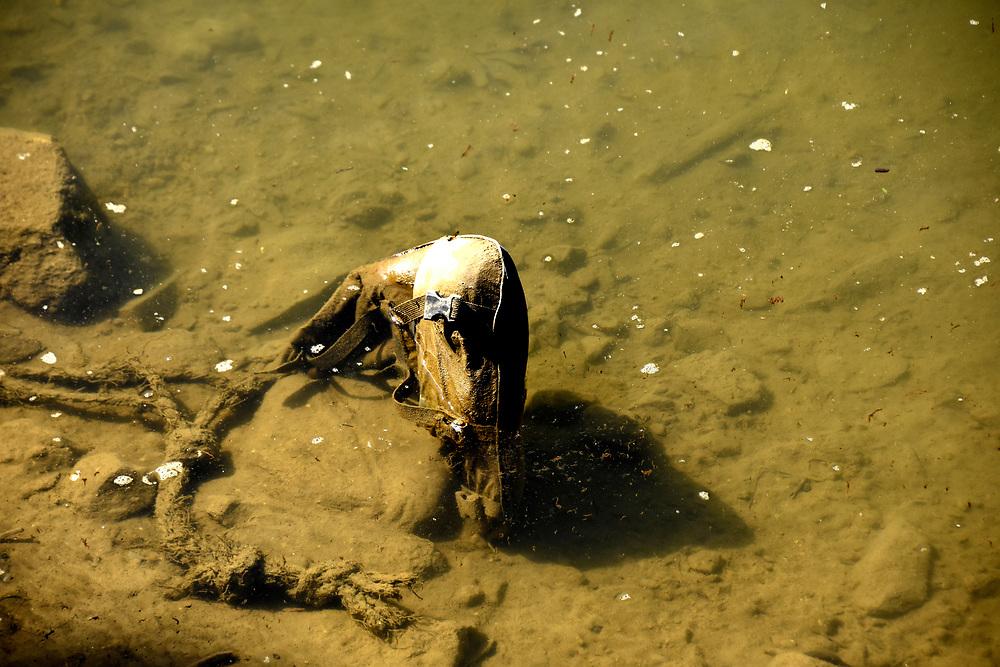 Rubbish rotting on the lake bed of Lake Pewa, Pokhara, Nepal