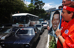 Aura Rosales points to a picture of Chavez as motorists pass the presidential palace as she celebrates outside the presidential palace.  Early that morning the National Electoral Council announced that preliminary results showed Chavez had defeated a presidential referendum by about 16 points.  Opposition leaders claim election fraud, though the Organization of American States and Carter Center said the election was clean.