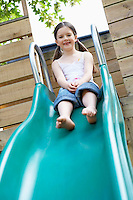 Little girl on top of slippery slide portrait