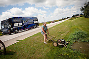 Linda Oldenkamp mows her lawn as Republican presidential candidate, Rep. Michele Bachmann's campaign bus passes by in Sanborn, Iowa, August 9, 2011.