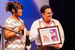 Tito Puente, Jr. and his Orchestra perform at the Reichhold Center of the Arts.  Puente's performance marks 25 years and 3 days since his father, renowned Latin jazz and salsa musician performed on this same stage for a Virgin Islands audience.  Director Nissa N. Copemann presents Tito with a gift commemorating the occasion.  Tito Puente, Jr. nurtures his father's musical legacy by performing the classic compositions for which he was known.  throughout © Aisha-Zakiya Boyd