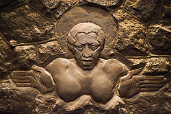 Stone carving of Pele, the Hawaiian goddess of fire, inset above the fireplace of Volcano House, located in Hawaii Volcanoes National Park on the Big Island of Hawaii.