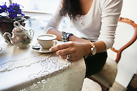 Midsection of woman having coffee at cafe