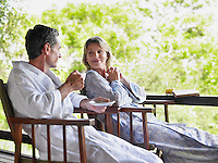 Adult couple sitting on terrace man holding cup smiling