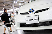 Visitors look at Toyota Motor Corp.'s third generation Prius hybrid car during an official unveiling of the vehicle at the automaker's showroom  was in Tokyo, Japan on 18 May 2009.