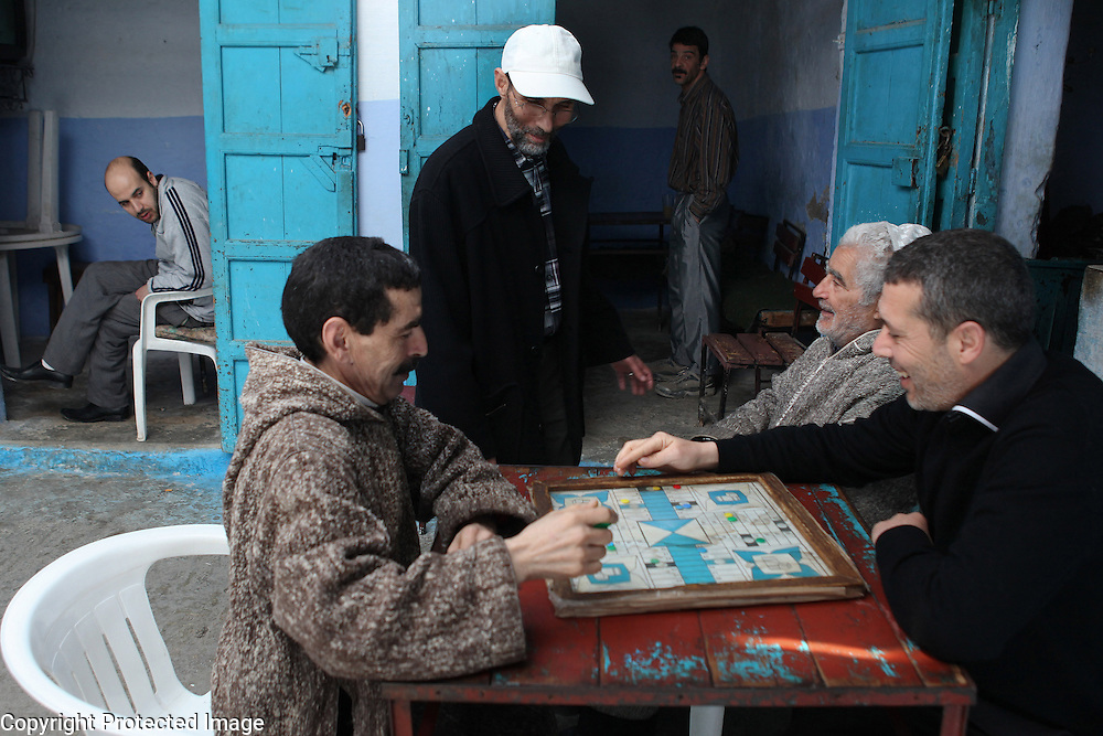 "Some men play a game of parcheesi outside a tea shop in Chefchaouen, Morocco, whose ""medina"" (old city) is famous for its striking blue walls."