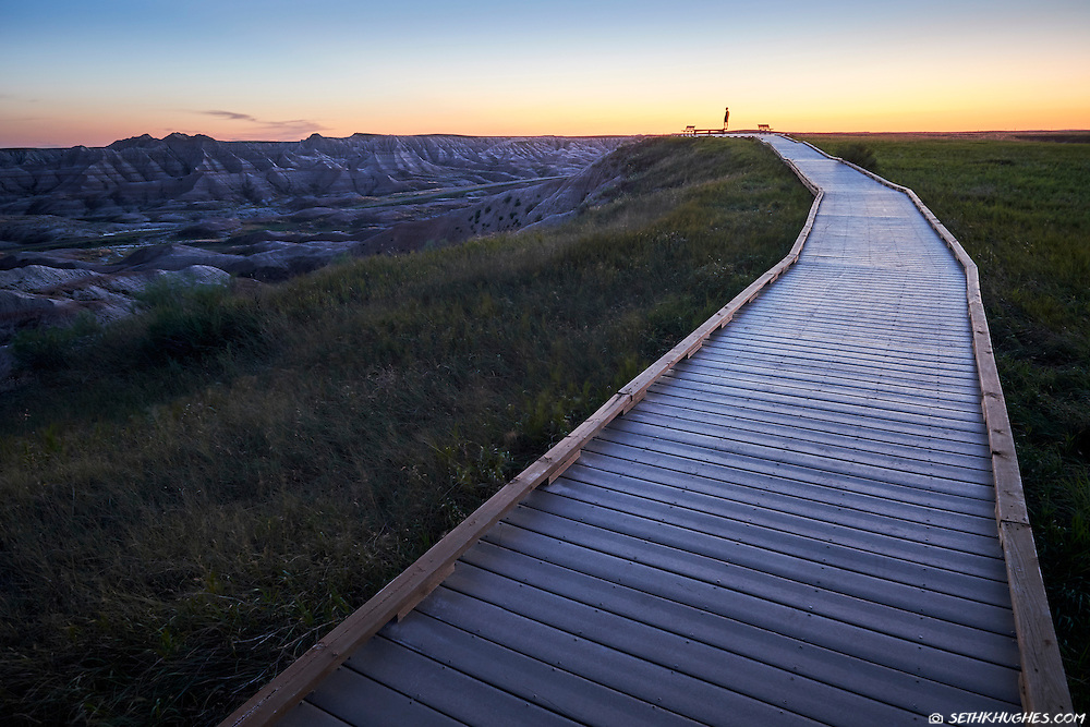 A silhouetted person stands in the distance at a viewpoint overlooking Badlands National Park, South Dakota.