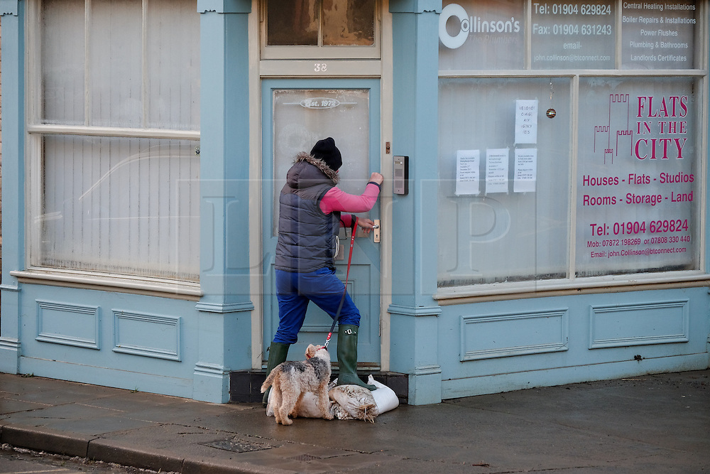 &copy; Licensed to London News Pictures. 29/12/15<br /> York, UK. <br /> <br /> A man enters his business as flood water begins to subside on Huntington Road in York. Further rainfall is expected over coming days as Storm Frank approaches the east coast of the country.<br /> <br /> Photo credit : Ian Forsyth/LNP