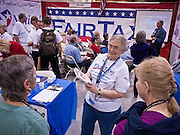 "A woman sells the Fair Tax book in the Fair Tax booth the Policy Summit in Phoenix, AZ, Friday. The Tea Party Patriots American Policy Summit starts in Phoenix Friday and goes through Sunday Feb. 27. About 2,000 people are expected to attend the event, which organizers said is meant to unite Tea Party groups across the country. Speakers include former Minnesota Governor Tim Pawlenty, Texas Congressman Ron Paul, former Clinton advisor Dick Morris and conservative blogger Andrew Brietbart. The event ends with a presidential straw poll Sunday. The ""Fair Tax"" movement advocates doing away with the income tax, social security tax, IRS and other taxing authorities and replacing them all with a national consumption or sales tax.   Photo by Jack Kurtz"