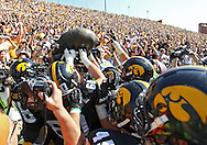 September 29 2012: The Iowa Hawkeyes grab the Floyd of Rosedale Trophy after the end of the NCAA football game between the Minnesota Golden Gophers and the Iowa Hawkeyes at Kinnick Stadium in Iowa City, Iowa on Saturday September 29, 2012. Iowa defeated Minnesota 31-13 to claim the Floyd of Rosedale Trophy.